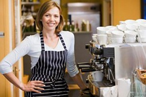 Womans standing near cappuccino machine at a cafe