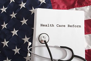 "American flag with stethoscope and ""Health Care Reform"" document"