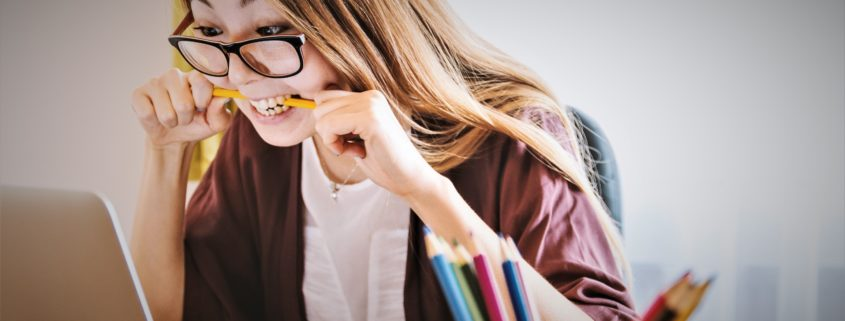 Woman wearing glasses and biting pencil while looking at laptop