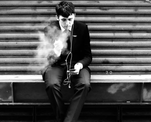 man on loading dock using e-cigarette