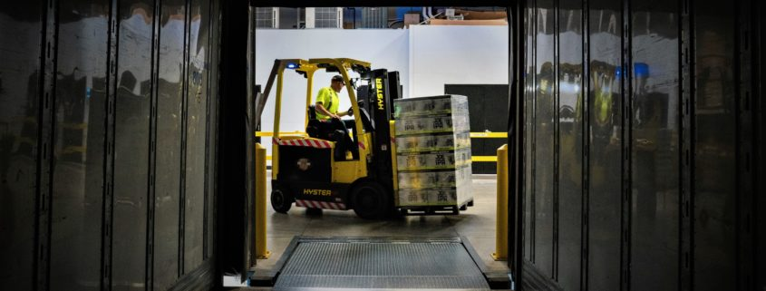 Worker driving a forklift in a warehouse