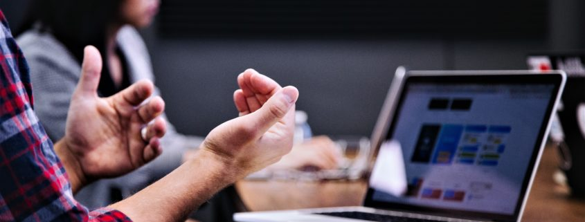 Man gesturing in front of his laptop at a meeting