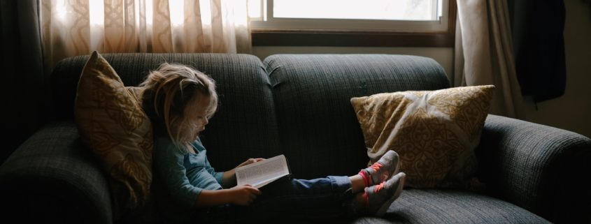 little girl reading on the sofa