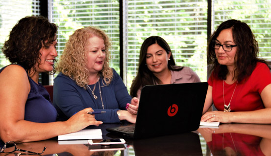 Group of woman in discussion standing around a laptop