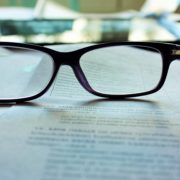 Reading glasses sitting on a paper contract