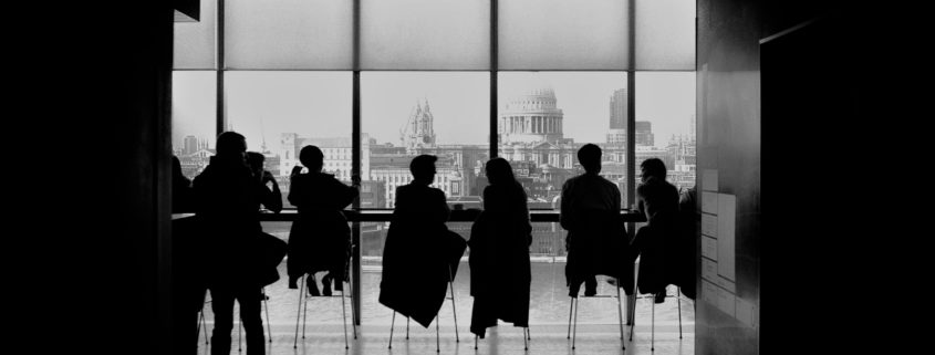 Black and white photo of people sitting at a long table looking out at city